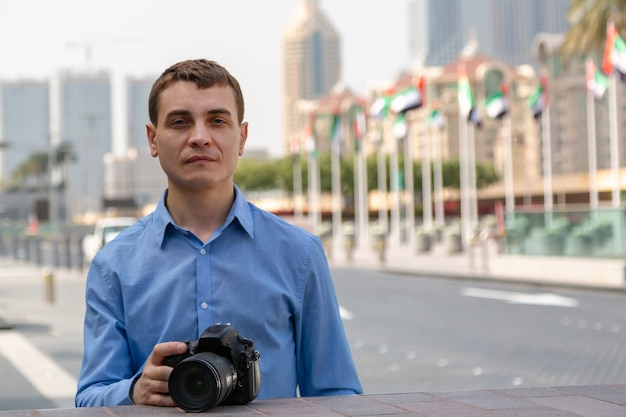 Um homem com roupas azuis está segurando uma câmera na cidade