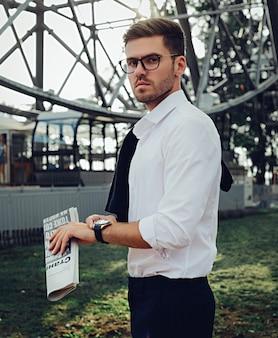 Um homem com roupas clássicas e óculos segurando um jornal