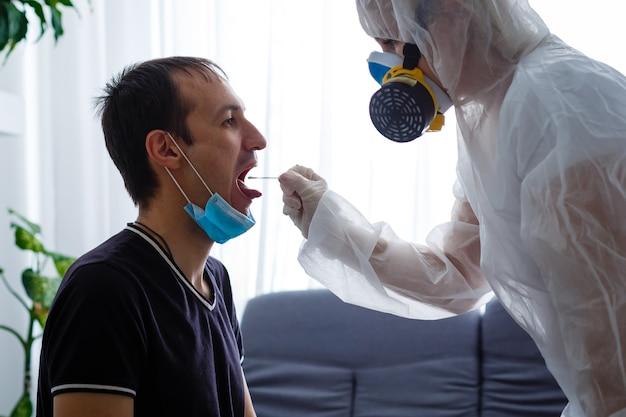 Um homem com roupas de proteção e luvas tira uma mancha de um homem mascarado.