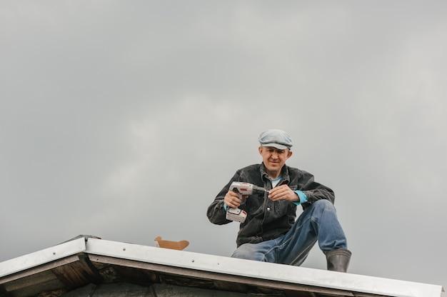 Um homem com roupas de trabalho aperta os parafusos com uma chave de fenda no telhado contra um céu nublado.