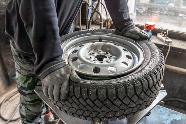 Um homem com roupas de trabalho e luvas conserta um carro coloca pneus de inverno