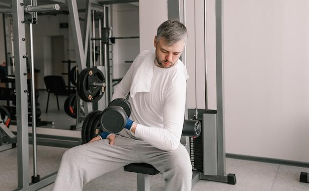 Um homem com roupas leves, sentado em um banco, levanta halteres no ginásio. fisiculturista novato