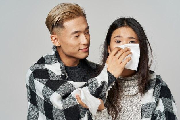 Um homem com roupas quentes cuidando de uma mulher asiática doente
