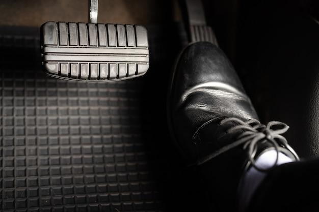 Um homem com sapatos de couro está pisando no acelerador de um carro.