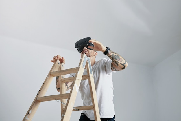 Um homem com tatuagens em uma camiseta branca em branco e um fone de ouvido vr subindo uma escada em uma sala com paredes brancas