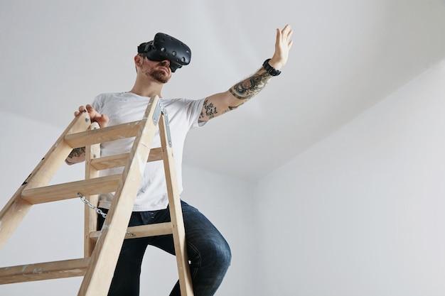 Um homem com tatuagens, vestindo uma camiseta branca lisa e óculos de realidade virtual no topo de uma escada de madeira jogando um jogo de realidade virtual