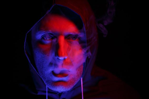 Um homem com traje de proteção exala fumaça. conceito de imagem de halloween. proteção contra vírus. iluminado com luzes coloridas