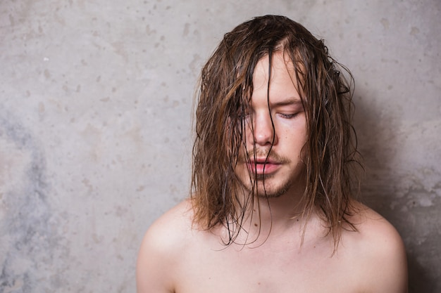 Um homem com um bigode e uma barba com longos cabelos molhados no fundo das paredes cinza, copyspace.