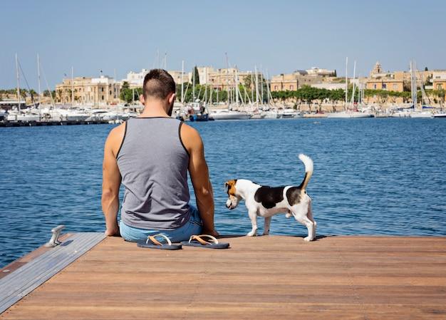 Um homem com um cachorro andando no cais flutuante