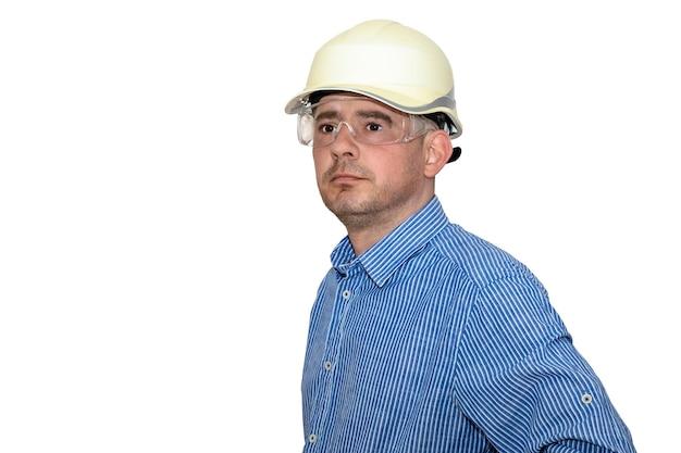 Um homem com um capacete de construção e uma camisa azul sobre um fundo branco e isolado. olhando para longe. brigadeiro. construtor. engenheiro. chefe.