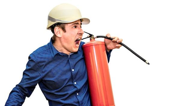 Um homem com um capacete de construção em uma parede branca isolada segura um extintor de incêndio nas mãos e grita. o capataz. construtor. engenheiro. precauções de segurança.