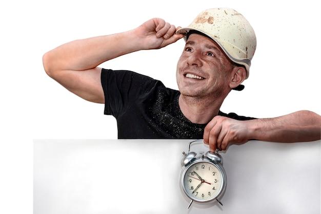 Um homem com um capacete de construção segura-o com uma das mãos e um despertador na outra