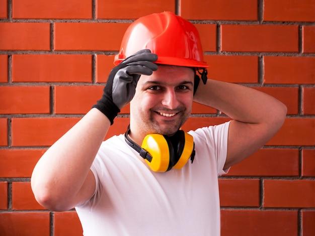 Um homem com um capacete de proteção e luvas pretas contra uma parede de tijolo vermelho, com fones de ouvido que reduzem o ruído em volta do pescoço. conceito de bricolage e segurança. diy faça você mesmo