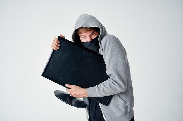 Um homem com um capuz cinza disfarça o hacker de técnica de roubo.