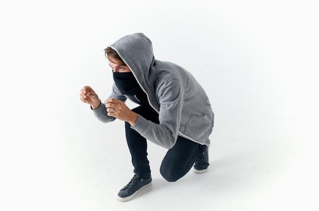 Um homem com um capuz com uma balaclava no rosto anonimato crime roubo