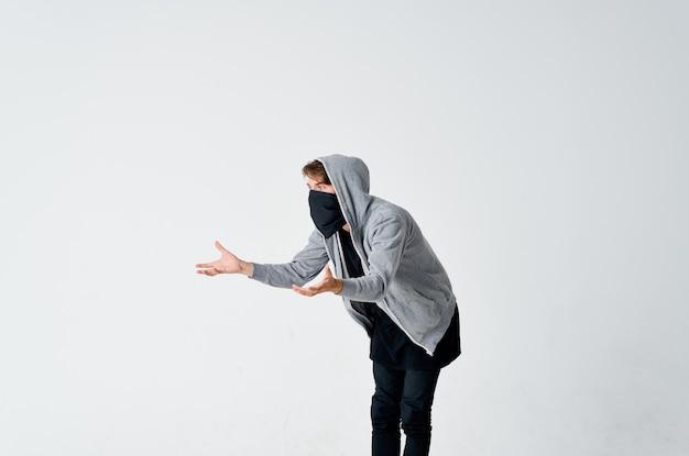 Um homem com um capuz com uma máscara esconde seu rosto valentão roubo de anonimato