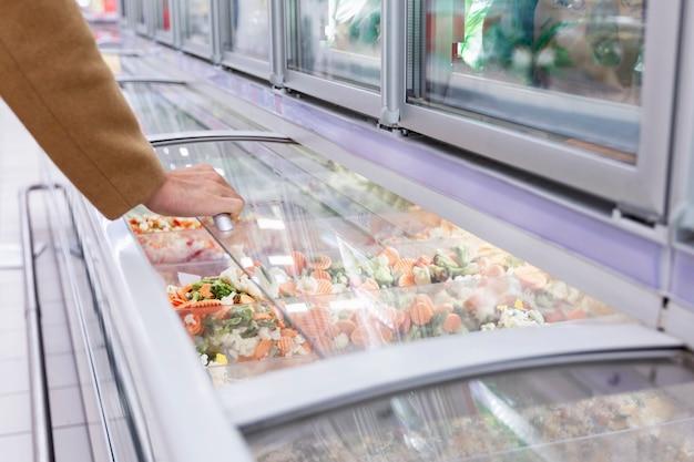 Um homem com um casaco bege na seção de alimentos congelados de um grande supermercado abre uma geladeira de vegetais. fechar-se.