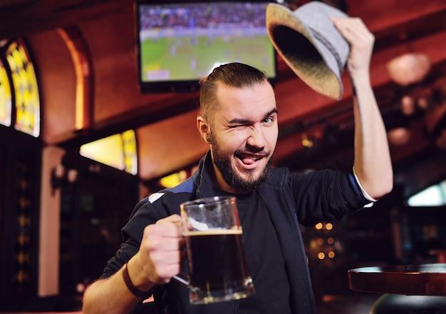 Um homem com um chapéu da baviera, bebendo cerveja em um pub e assistindo futebol em um monitor durante a oktoberfest