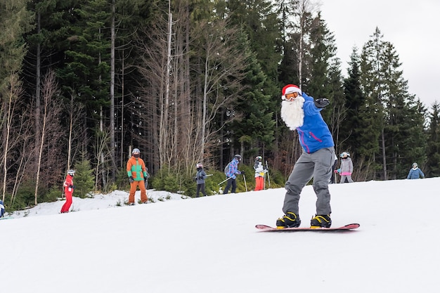 Um homem com um chapéu de papai noel com uma prancha de snowboard em uma estação de esqui.