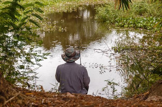 Um homem com um chapéu lança uma vara de pescar em um pequeno lago