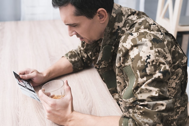 Um homem com um copo de álcool e uma foto de um militar.