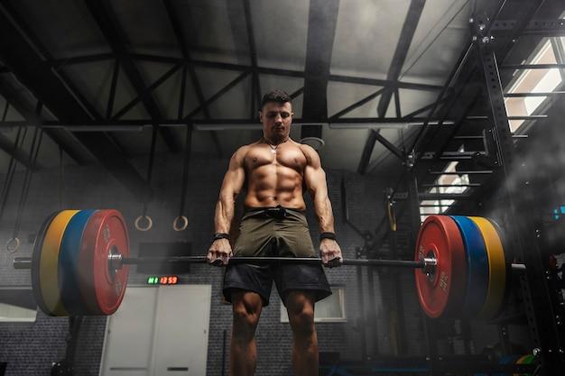 Um homem com um corpo forte segura uma barra pesada e faz um levantamento terra em um ginásio de atmosfera escura.