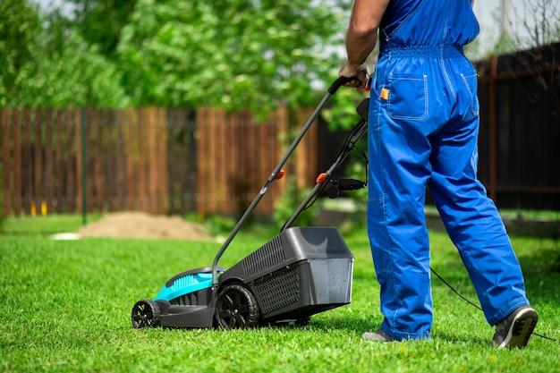 Um homem com um cortador de grama elétrico cortando a grama