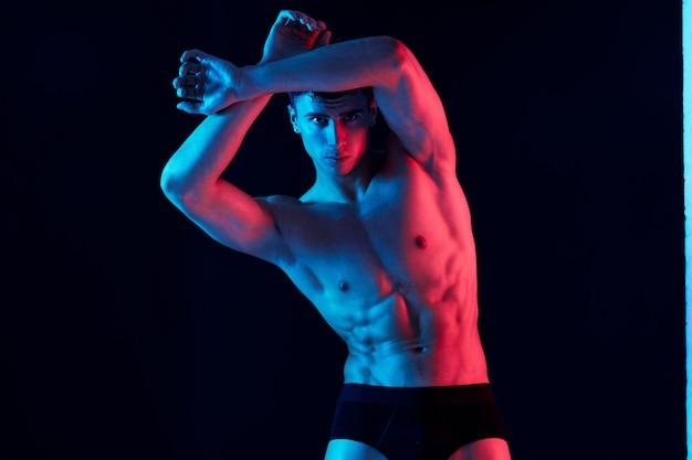 Um homem com um físico atlético inclinou-se para o lado e um fundo preto luz neon