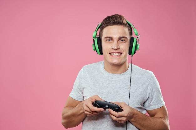 Um homem com um joystick nas mãos, fones de ouvido jogando jogos, entretenimento, estilo de vida, camiseta branca, fundo rosa