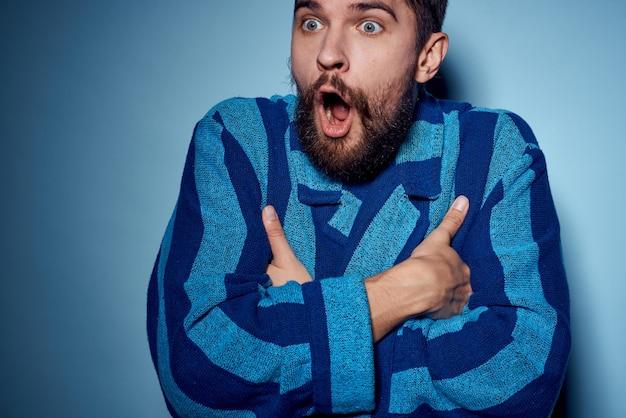 Um homem com um manto azul sobre um fundo claro gesticula com as mãos como modelo de roupa para casa. foto de alta qualidade