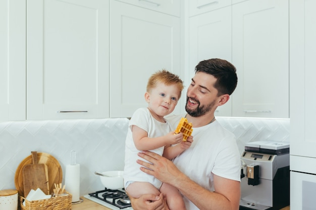 Um homem com um menino prepara o café da manhã, um pai e um filho