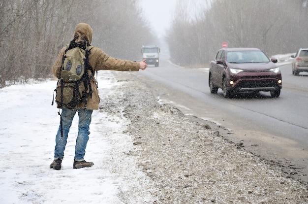 Um, homem, com, um, mochila grande, mostrando, polegares cima, para, hitchhiking