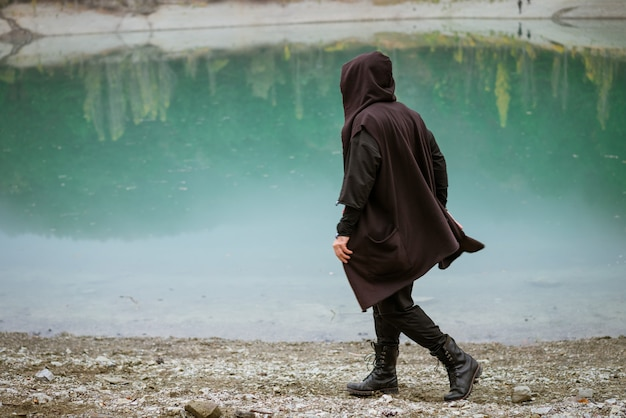 Um homem com um moletom com capuz caminha sozinho na praia perto de um lago calmo em uma área arborizada em algum lugar ...