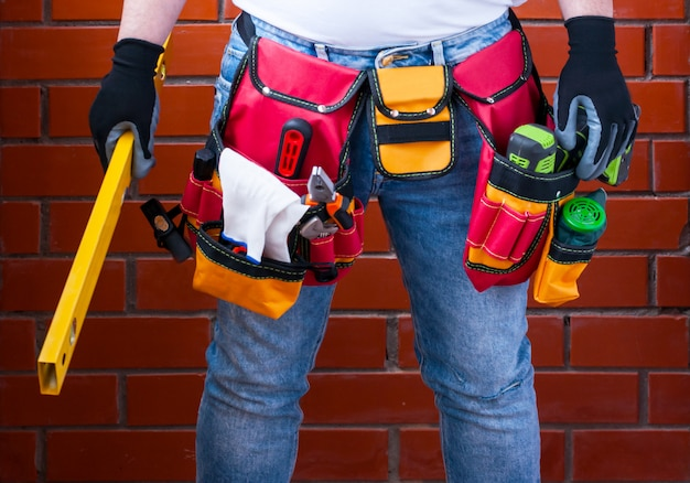 Um homem com um nível ereto em sua mão na perspectiva de uma parede de tijolo vermelho com uma maleta de ferramentas completa.