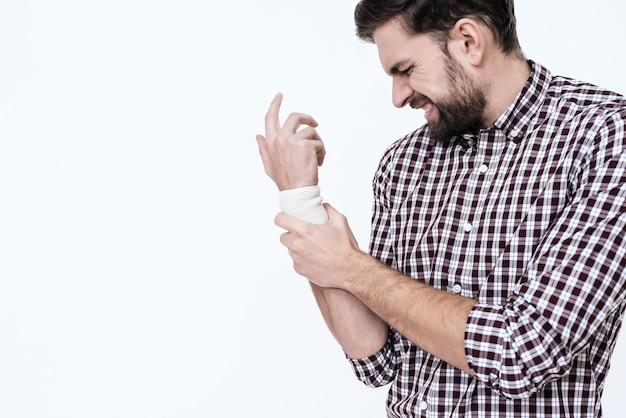 Um homem com um pincel enfaixado sente dor.