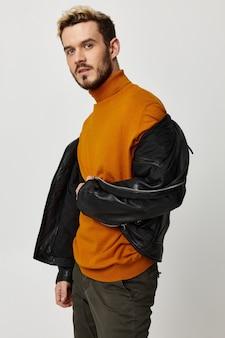 Um homem com um suéter laranja virou-se de lado para a câmera em um fundo claro e uma capa de couro