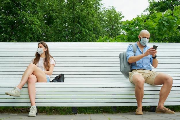 Um homem com um telefone e uma mulher sentados em extremos opostos do banco, mantendo distância um do outro para evitar a propagação do coronavírus.