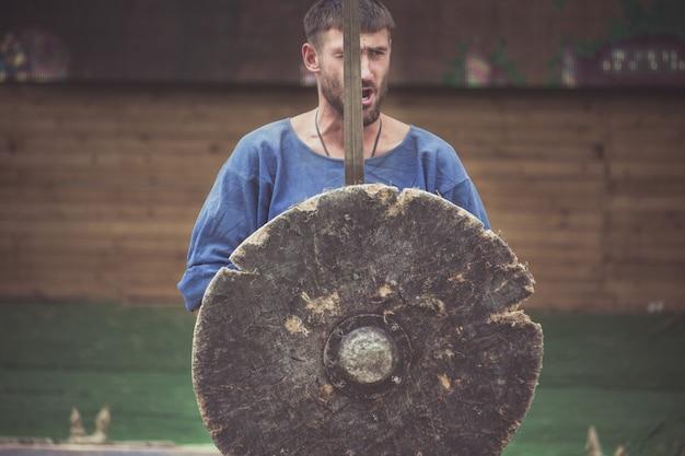 Um homem com um traje viking segura uma espada e um escudo