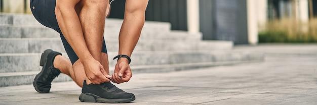 Um homem com um uniforme atlético leve amarra uma renda em um sapato para correr