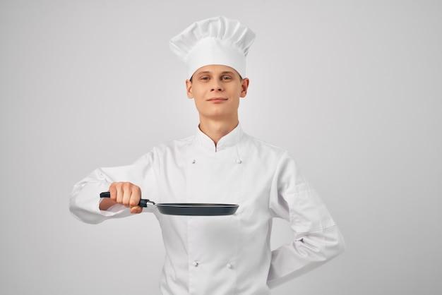 Um homem com um uniforme de chef de cozinha, uma frigideira na mão, cozinhando comida na cozinha