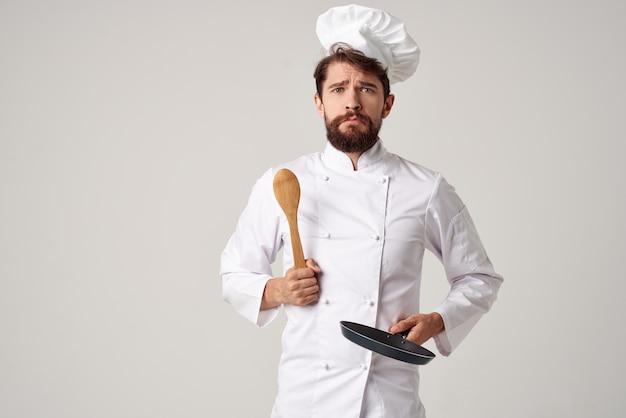 Um homem com um uniforme de chef de cozinha, uma frigideira nas mãos, cozinhando o trabalho