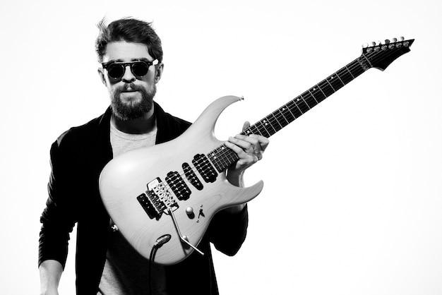 Um homem com um violão, uma jaqueta de couro preta e óculos escuros sobre um fundo claro