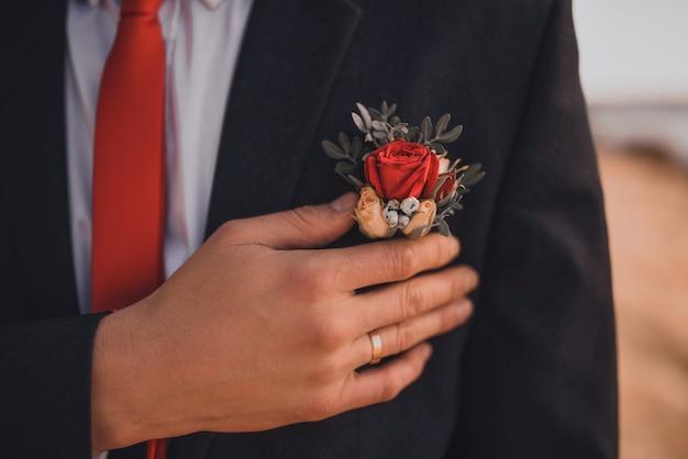 Um homem com uma aliança no dedo segura uma flor na lapela em sua jaqueta. mãos dos noivos em close-up