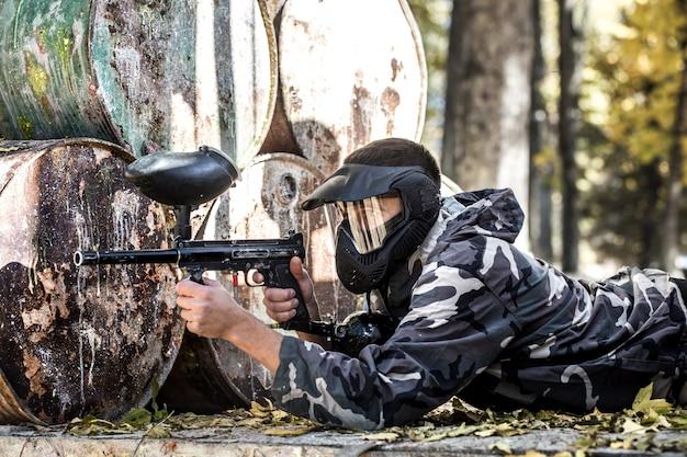 Um homem com uma arma jogando paintball.