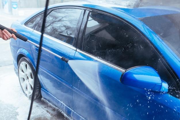 Um homem com uma arma lava o carro. lavagem de carros self-service