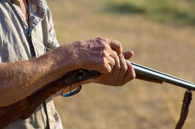 Um homem com uma arma nas mãos e um colete verde em uma caça ao faisão em uma área arborizada