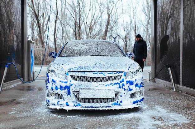 Um homem com uma arma para aplicar espuma no carro. lavagem de carros self-service