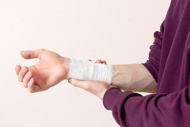 Um homem com uma bandagem branca no braço, dor e ferimentos médicos, sensação de dor