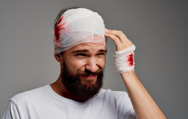 Um homem com uma bandagem de sangue na cabeça no braço operação fundo cinza camiseta branca