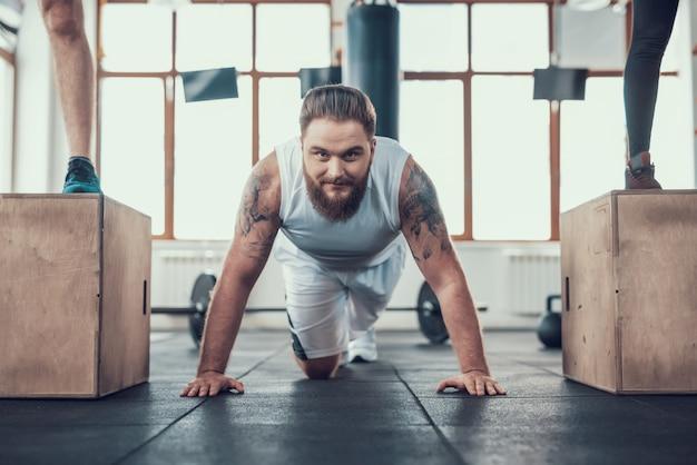 Um homem com uma barba faz exercício no ginásio.